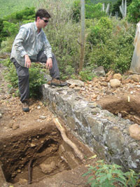 Archaeologist John Chenoweth looks at the house foundation.