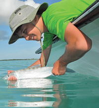young angler releases a bonefish